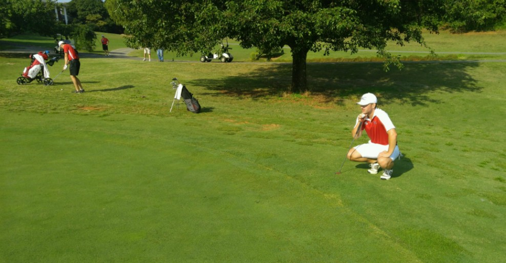 Pictured: Freshman Brandon Noland reading the green after a notable 74 on the 1st day of competition